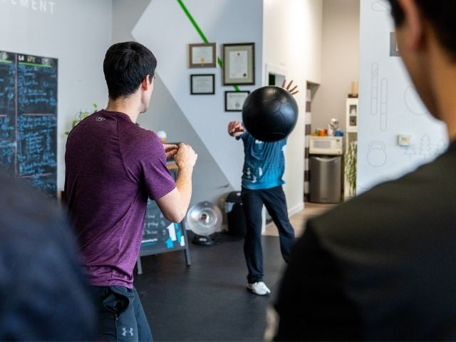 Vancouver chiropractor receiving a medball pass from a physio